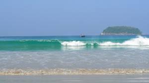 Лодка на волнах на пляже Ката на фоне острова Koh Poo